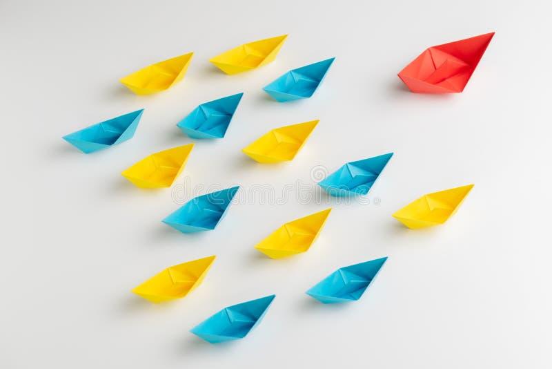 Influencer、KOL、关键民意领袖或者领导概念,大红色origami纸船在其他前面带领小黄色和 免版税库存照片