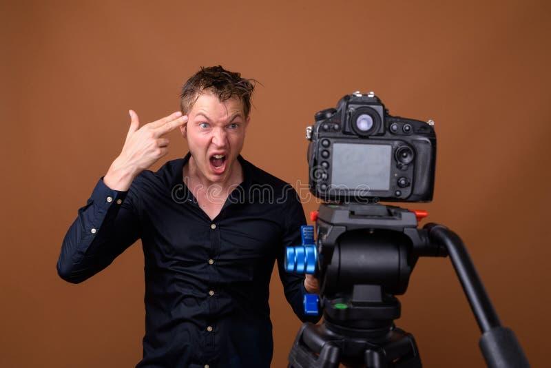 Influencer молодого человека vlogging с камерой DSLR в студии пока делающ смешную сторону стоковые фото