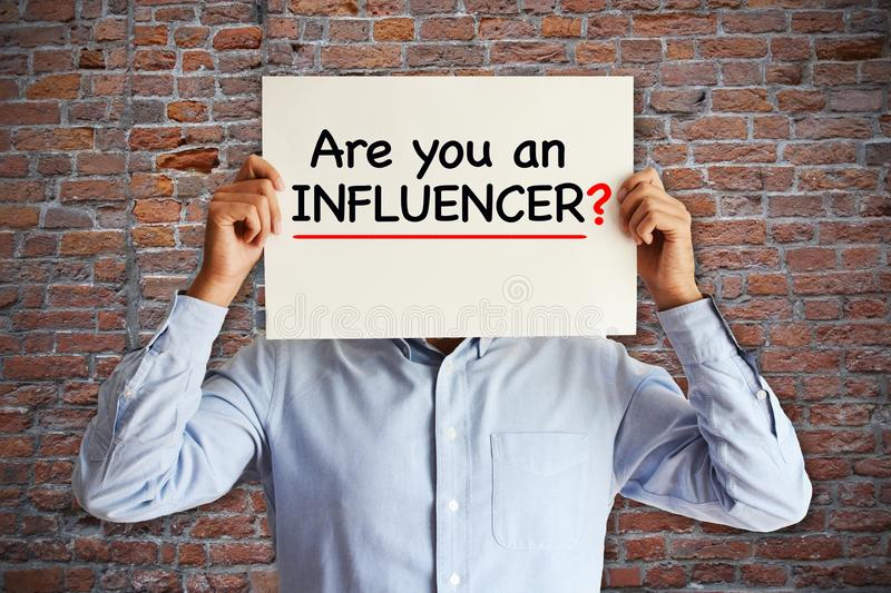 "Influencer marketing concept with ""are you an influencer"" question on white paper in young blogger's hands royalty free stock image"