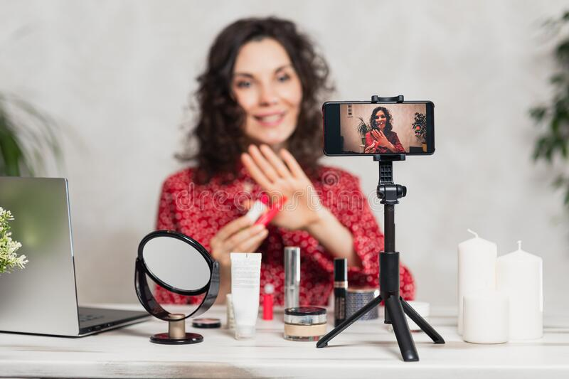Influencer Young girl blogger talks about makeup. Woman recording video blog tells how to be beautiful. Bloger talks facial beauty stock image