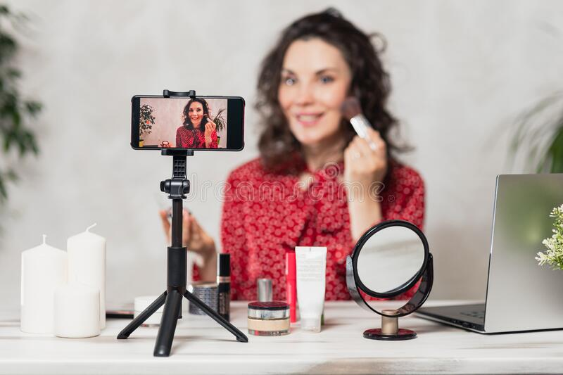 Influencer Young girl blogger talks about makeup. Woman recording video blog tells how to be beautiful. Bloger talks facial beauty stock photo