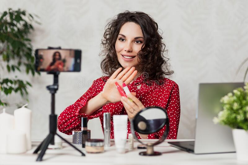 Influencer Young girl blogger talks about makeup. Woman recording video blog tells how to be beautiful. Bloger talks facial beauty royalty free stock photo