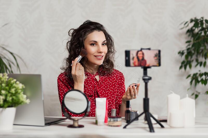 Influencer Young girl blogger talks about makeup. Woman recording video blog tells how to be beautiful. Bloger talks facial beauty royalty free stock photography