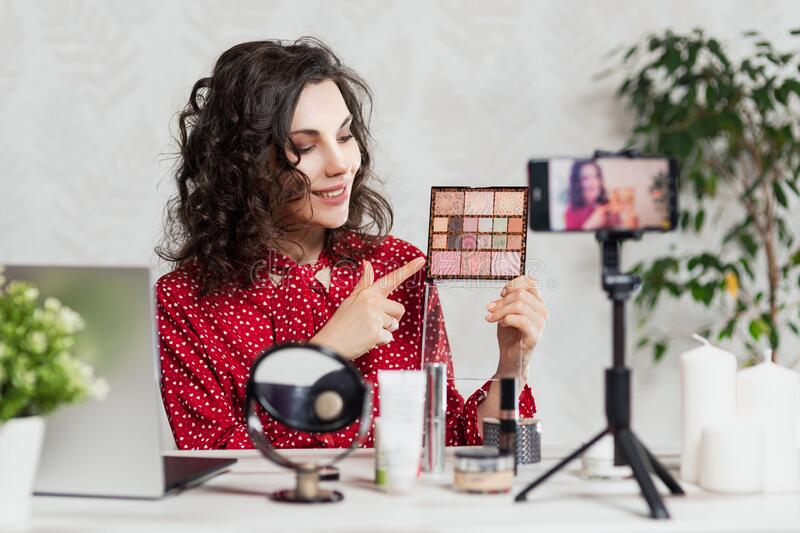 Influencer Young girl blogger talks about makeup. Woman recording video blog tells how to be beautiful. Bloger talks facial beauty stock images