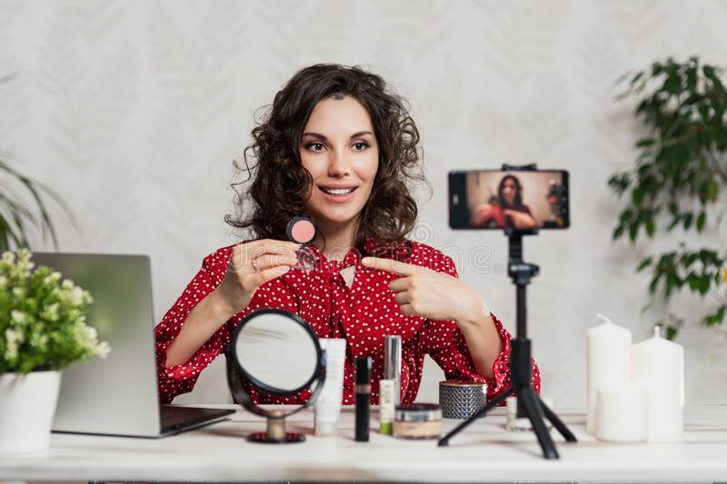 Influencer Young girl blogger talks about makeup. Woman recording video blog tells how to be beautiful. Bloger talks facial beauty royalty free stock image