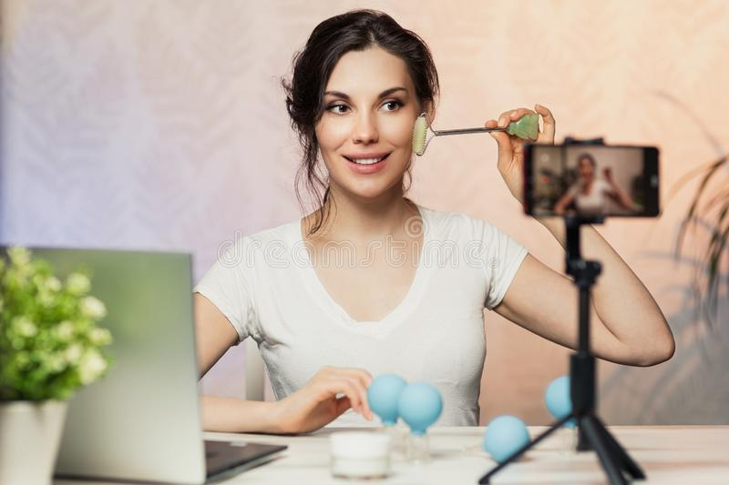 Influencer Young girl blogger talks about skincare. Woman recording video blog tells how to be beautiful. Bloger talks facial royalty free stock photography