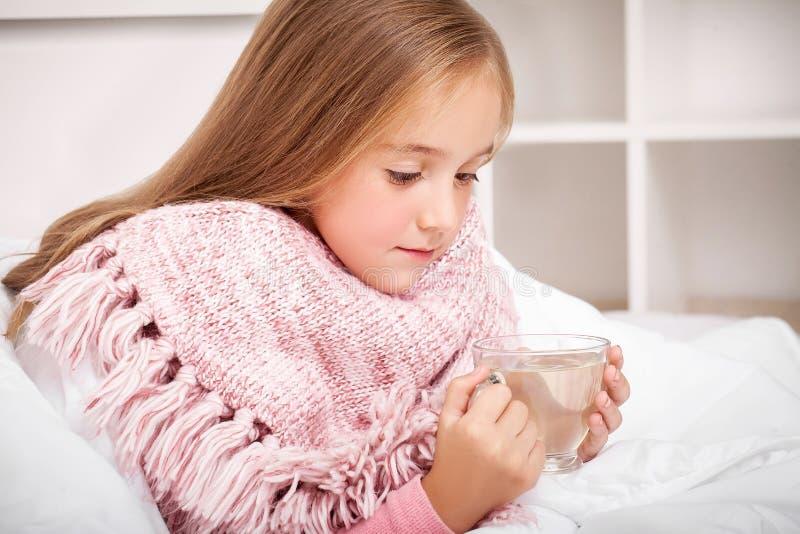 influensa Sjuk liten flicka med varmt citronte royaltyfri fotografi