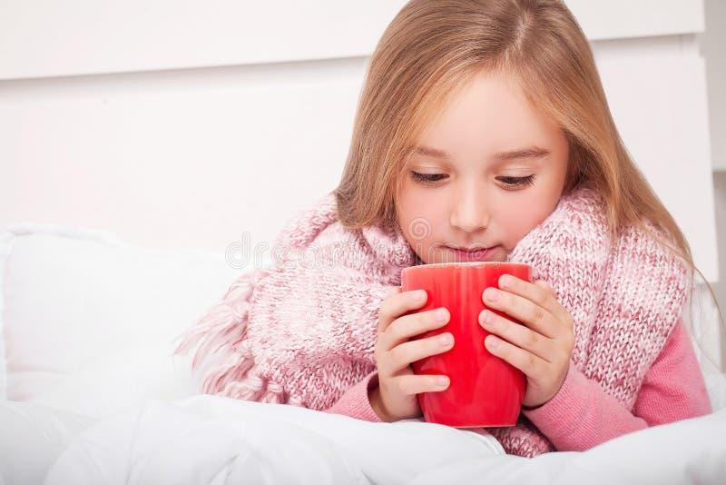influensa Sjuk liten flicka med varmt citronte arkivbilder