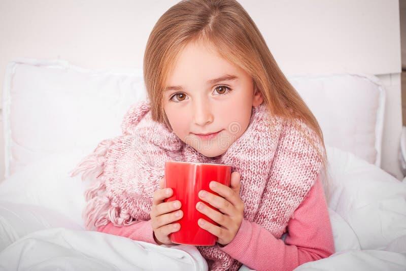 influensa Sjuk liten flicka med varmt citronte arkivfoton