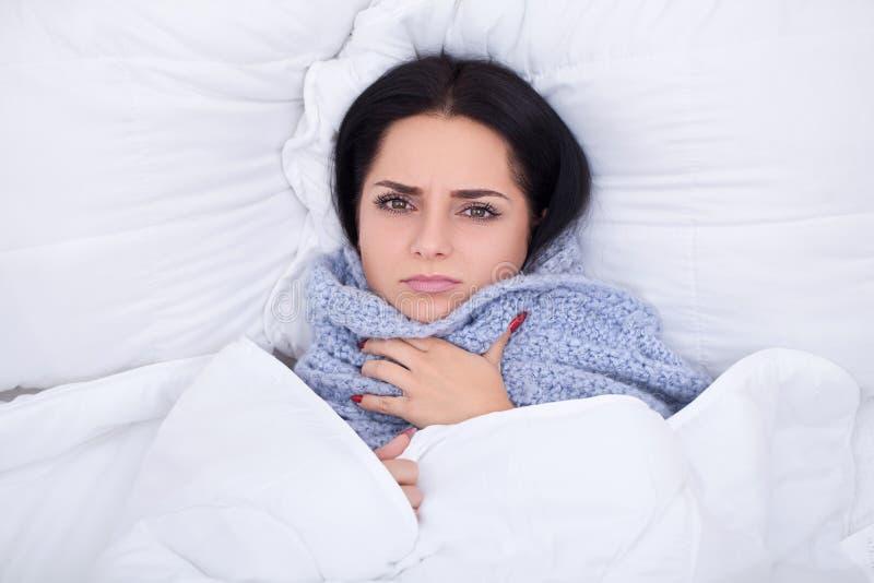 influensa Sjuk ung kvinna som hemma vilar i sängen arkivfoton