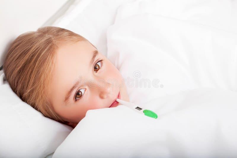 influensa Ung flicka som ligger i säng med en termometer fotografering för bildbyråer