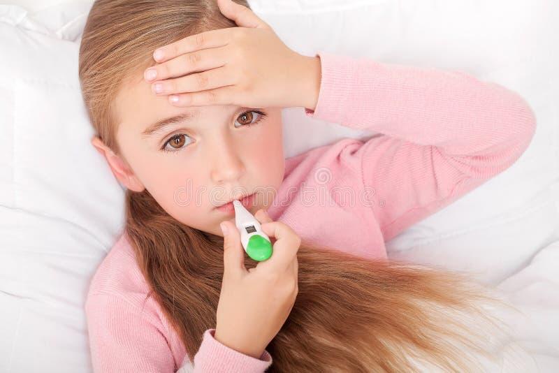 influensa Ung flicka som ligger i säng med en termometer arkivfoto