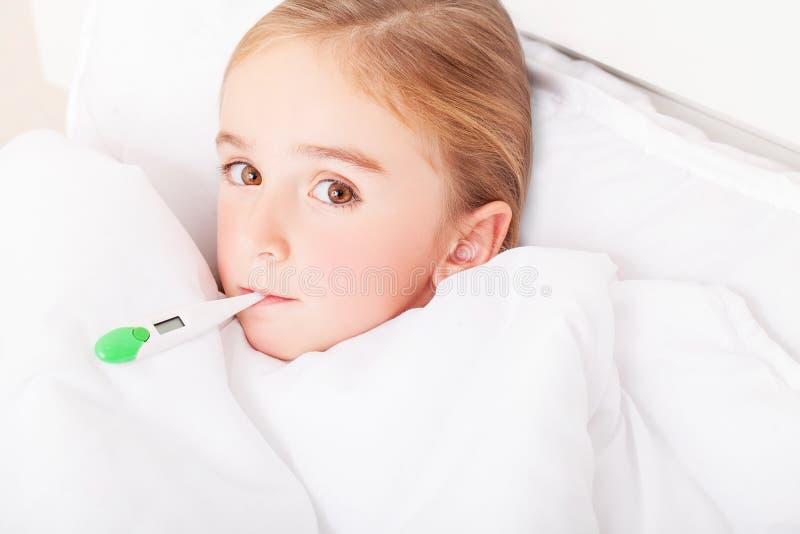 influensa Ung flicka som ligger i säng med en termometer royaltyfria foton