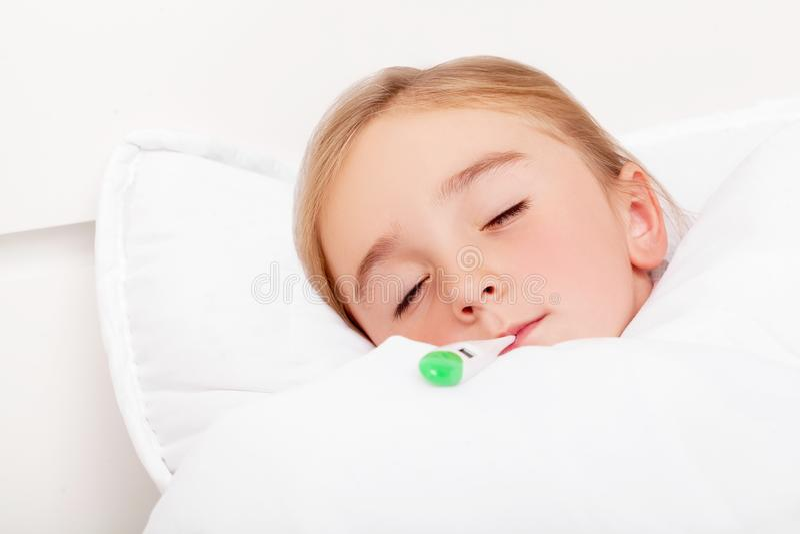 influensa Ung flicka som ligger i säng med en termometer arkivbild