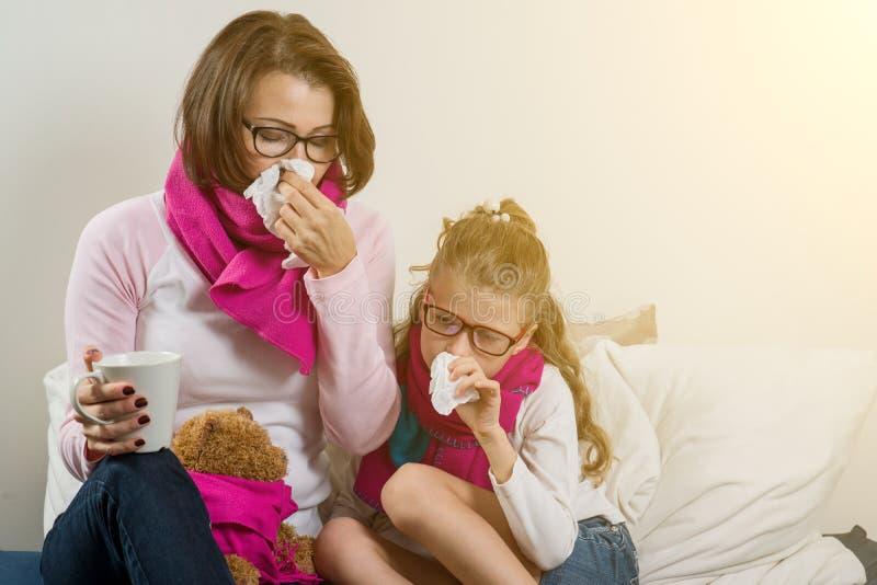 Influensasäsong, sjuk moder och barn hemma royaltyfri bild