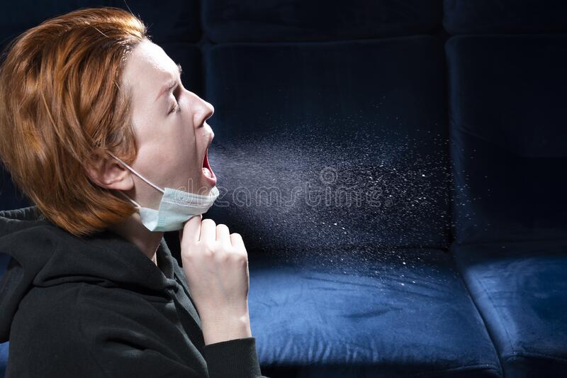 Influenza, cold, coronavirus. Infection through an airborne droplet. Girl in a hood and in a medical mask in front of a cloud of drops in the air royalty free stock photos