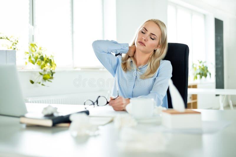 Influenza di sofferenza della giovane donna di affari sul lavoro fotografie stock