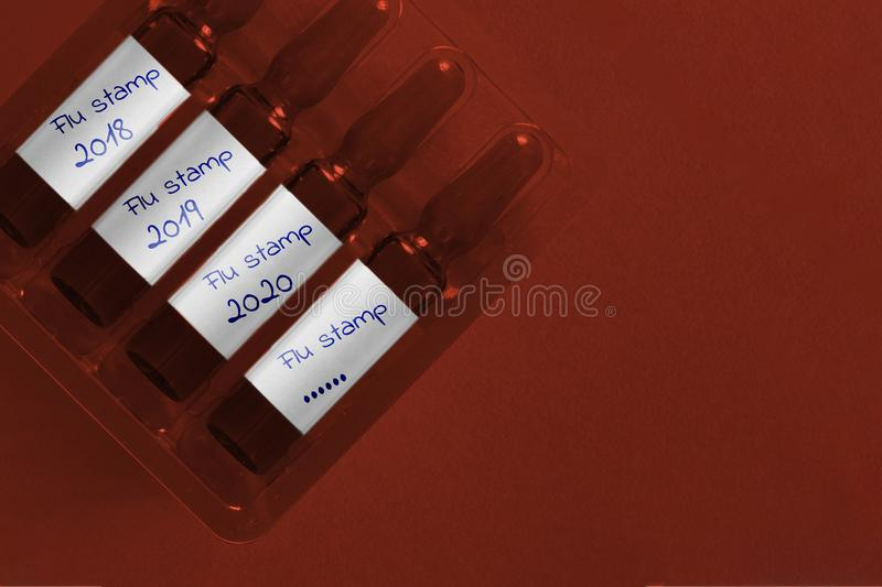 Influenza epidemic concept. Four ampules with overlay hand written inscription of new Flu Stamp and years. Pharma biotechnology. Banner stock images