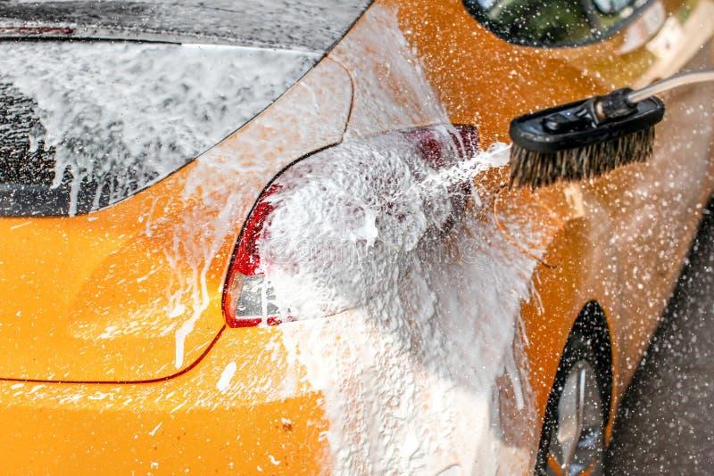 Influten carwash för gul bil, tvålannonsskum som besprutar droppar till solen royaltyfri fotografi