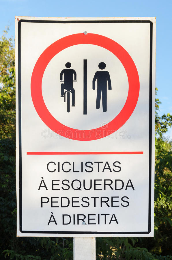 Info board in Portuguese signaling where cyclists and pedestrian. Info board in Portuguese signaling that cyclists should ride on the left and pedestrians should stock image
