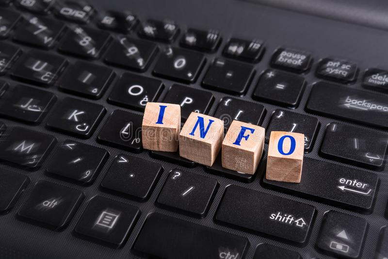 Info on laptop. Wooden block with Info word on laptop keyboard royalty free stock images