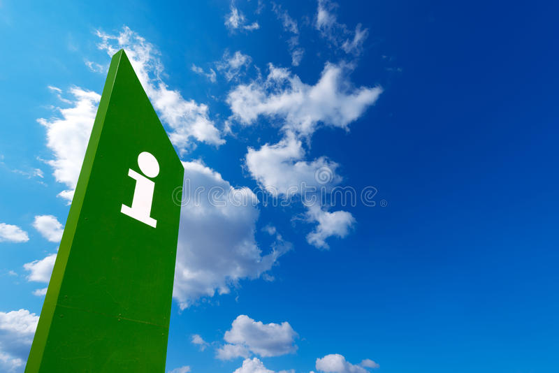 Info Point Barcelona Beach. Green billboard with symbol of tourist information on blue sky with clouds - Barceloneta beach in Barcelona, Spain royalty free stock images