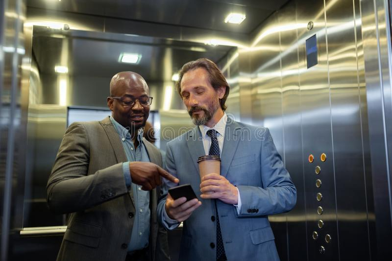 Two businessmen reading info on smartphone while using elevator. Info on smartphone. Two businessmen reading info on smartphone while using elevator in the royalty free stock images