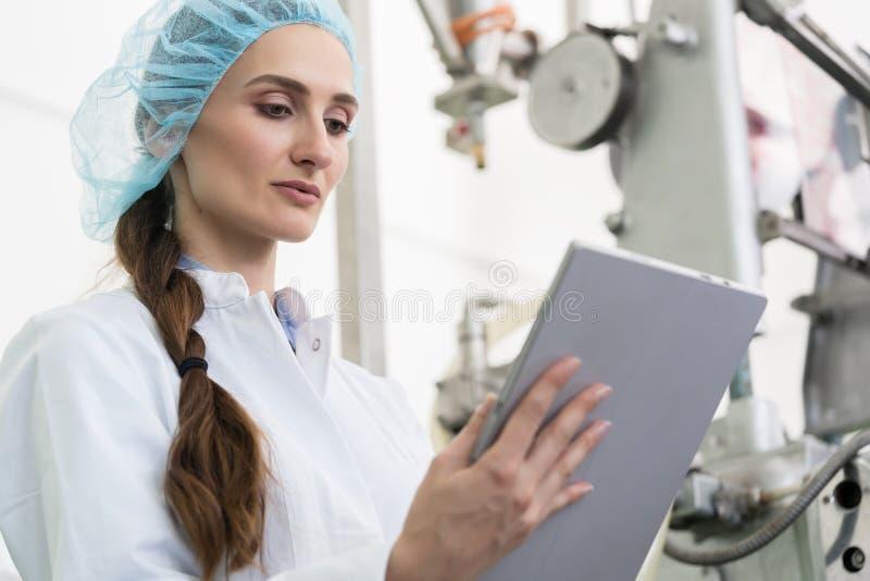 Informação de análise perita da mulher na tabuleta durante o trabalho na fábrica contemporânea fotos de stock