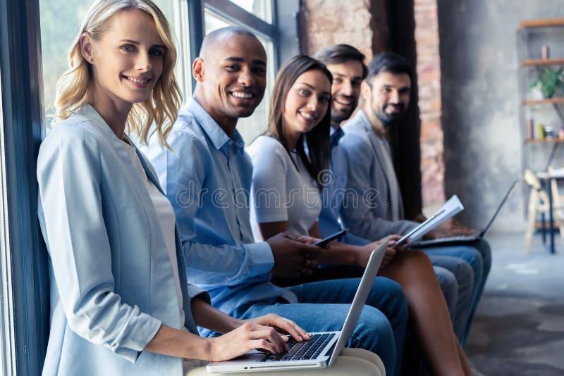 Informação realmente boa Grupo de jovens que sentam-se na conferência junto e no sorriso imagens de stock royalty free