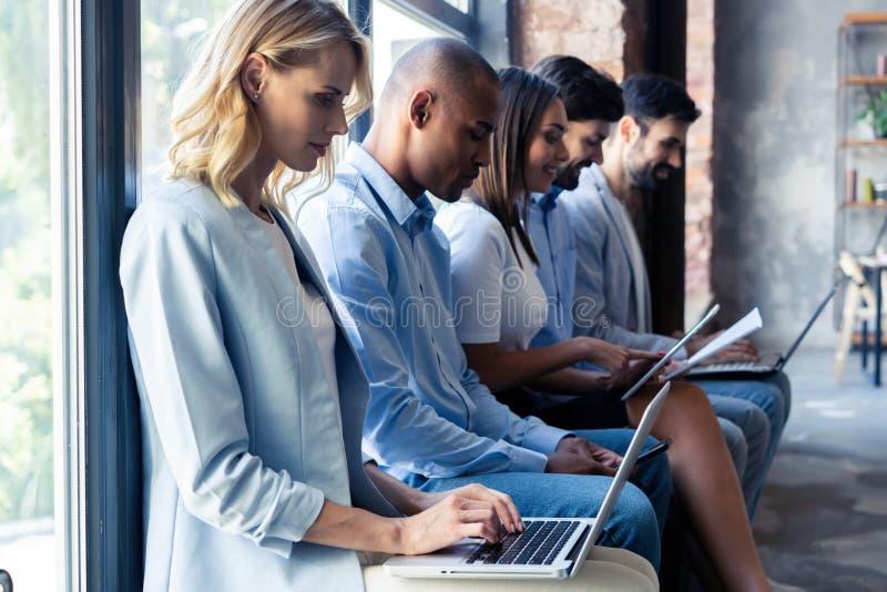 Informação realmente boa Grupo de jovens que sentam-se na conferência junto e no sorriso fotografia de stock