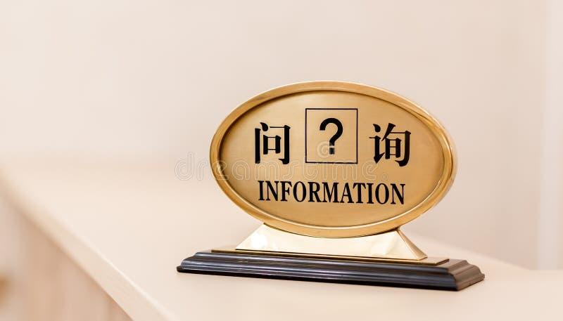 Información de la placa de identificación en otros idiomas: Inglés, japoneses, chinos Recepción del hotel, signo de interrogación fotografía de archivo libre de regalías