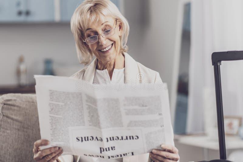 Información mayor sonriente de la lectura de la mujer sobre sucesos actuales fotografía de archivo libre de regalías
