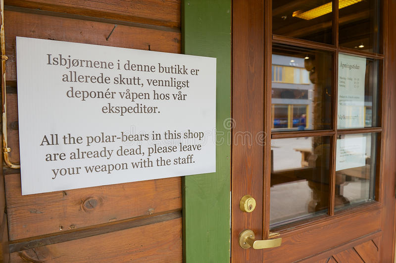 Informacja znak przy wejściem pamiątkarski sklep instruuje no wchodzić do z broniami w Longyearbyen, Norwegia obrazy royalty free