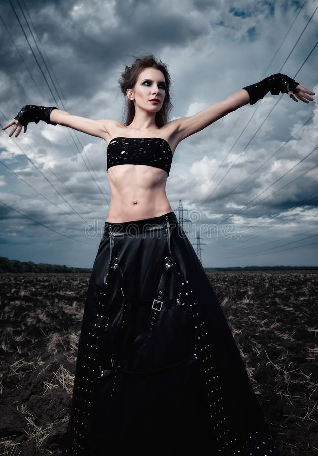 Informal fashion: beautiful slender young gothic girl dressed in black leather skirt and gloves. Outdoor portrait in field near. Informal fashion: the beautiful stock photography
