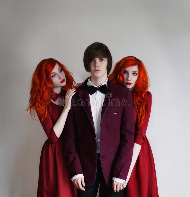 Informal guy with long hair in jacket and two twins with long red curly hair in red dress with bow tie on neck on white background stock photography