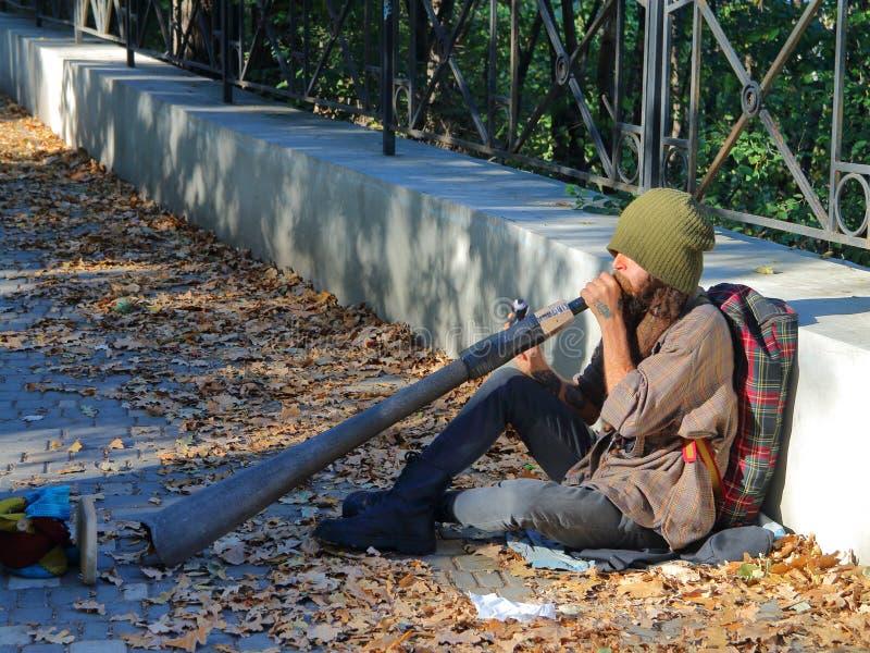 Informal street musician playing on Didgeridoo. stock photography
