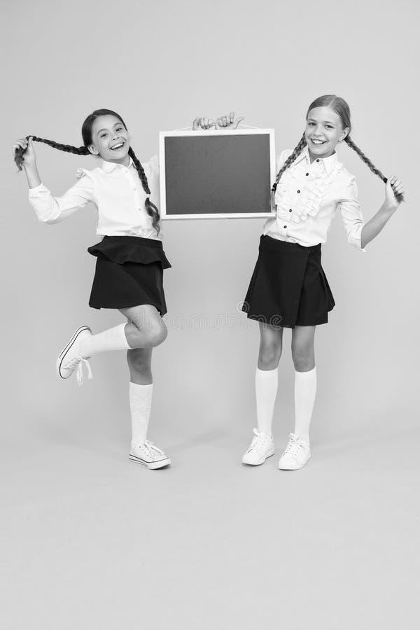Informando mudanças Meninas de escola alunos bonitos ocupam espaço na cópia do quadro Conceito de anúncio escolar Classmates imagens de stock royalty free