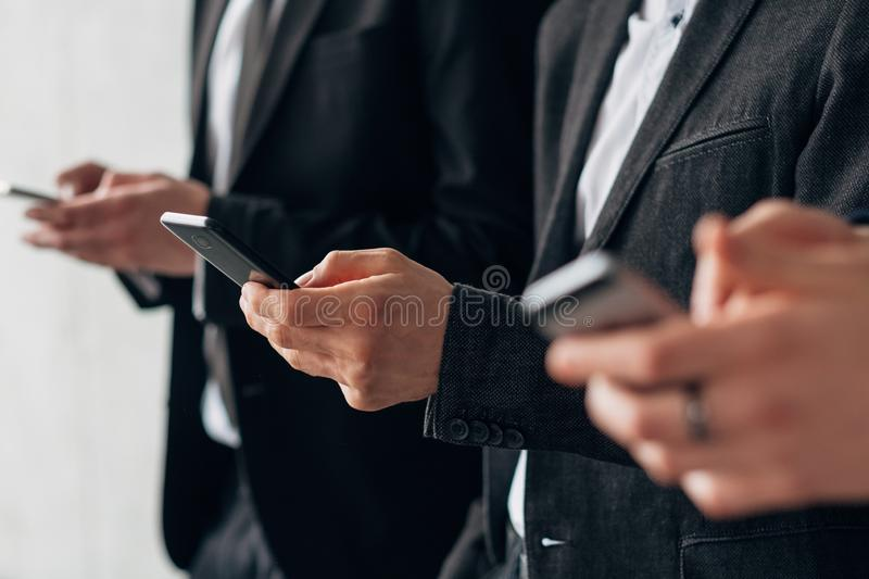 Information technology modern corporate world. Information technology in modern corporate world. Cropped shot of business men standing in row with smartphones stock photo