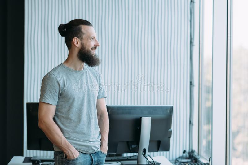 Information technology system administrator. Information technology. Portrait of successful system administrator standing at workplace, looking out window royalty free stock images