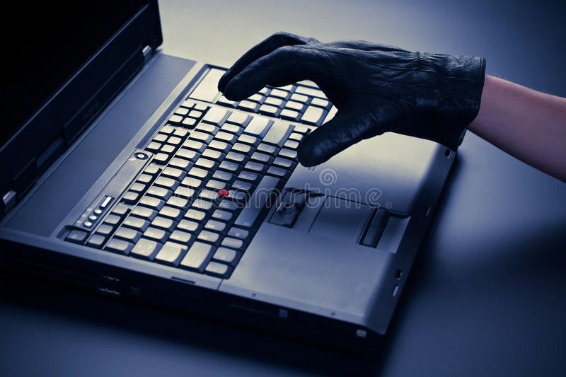 Information Theft. Concept image of a thief's hand over a business class mobile computer - security breach royalty free stock photography