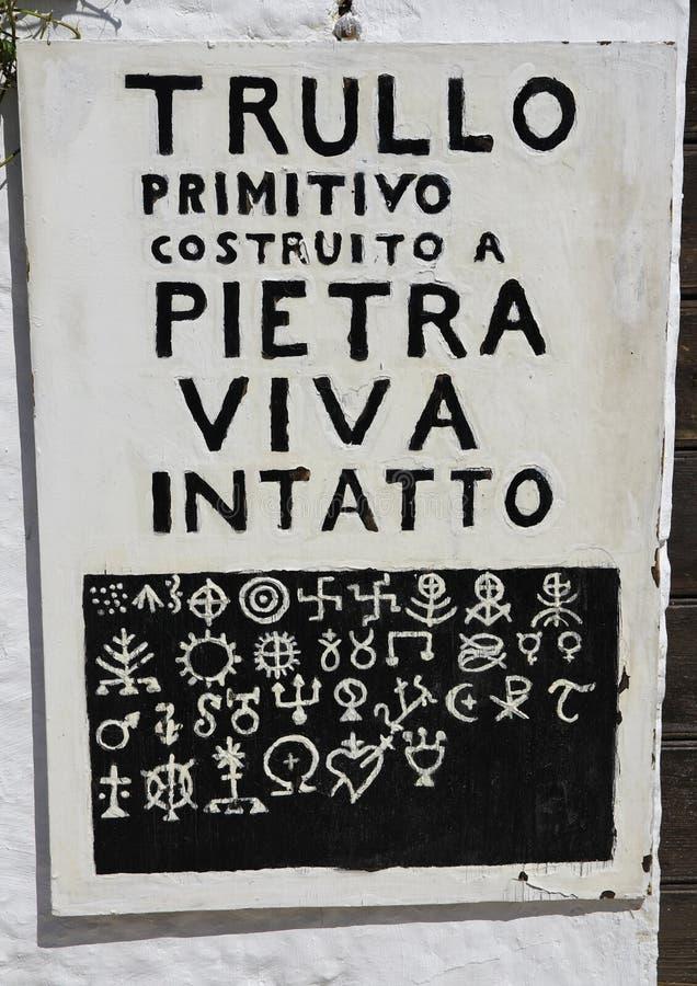 Informationsbräde med de mest bekanta symbolerna som målas på taken av en traditionell sten förlägga i barack trulli, Italien royaltyfria bilder