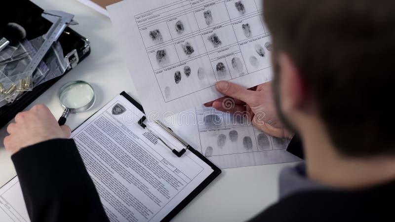 Informazioni d'esame delle impronte digitali dell'agente investigativo, facendo uso della lente d'ingrandimento, identità immagine stock libera da diritti