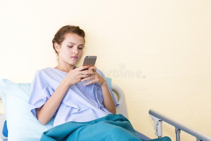 Informazioni di lavoro e di battitura a macchina del paziente attraente della giovane donna fotografia stock libera da diritti