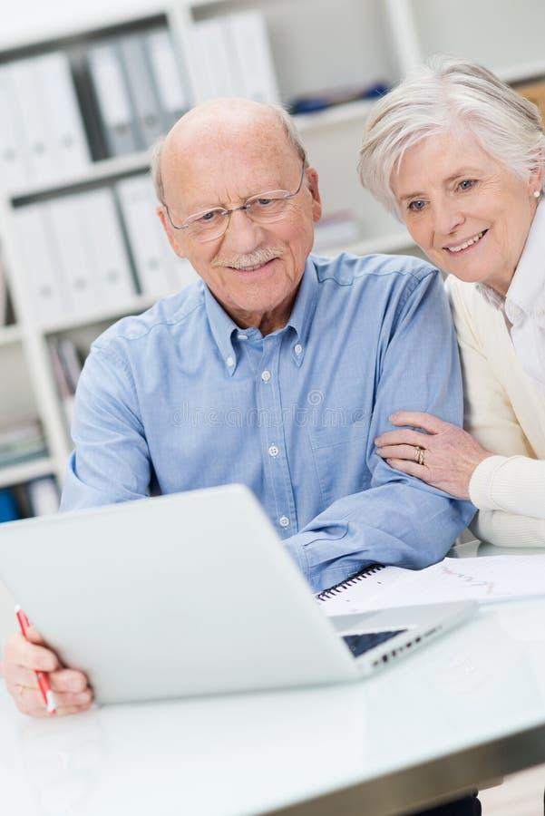 Informazioni senior della lettura delle coppie su un computer immagine stock