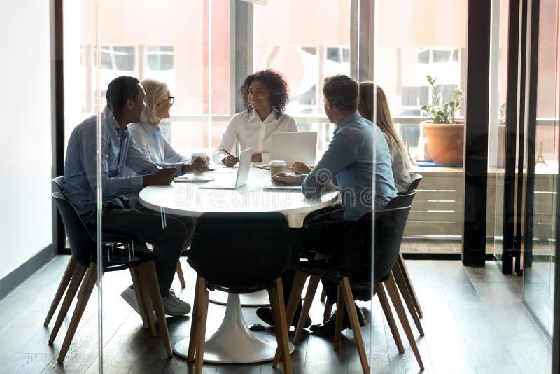 Informe afroamericano de la tenencia del jefe con los empleados en la sala de reunión foto de archivo