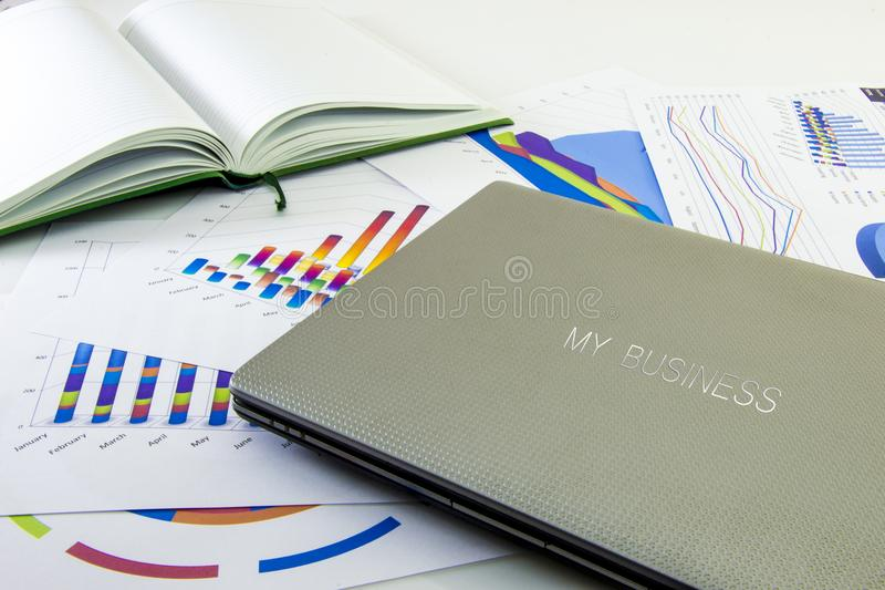 Informe anual, ordenador portátil y pluma del negocio con el fondo blanco imagenes de archivo