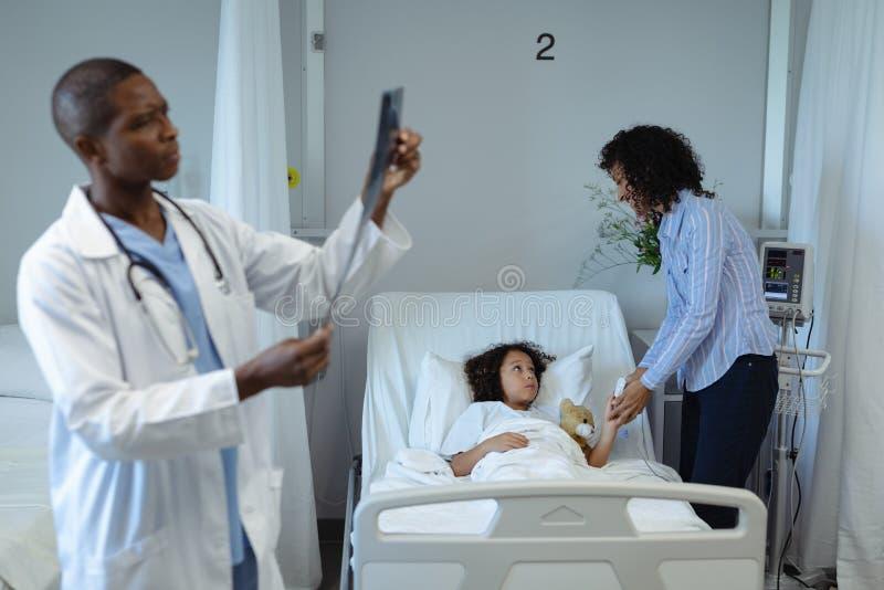 Informe de examen de la radiografía del doctor de sexo masculino mientras que madre que celebra sus manos de los hijos en la sala fotografía de archivo