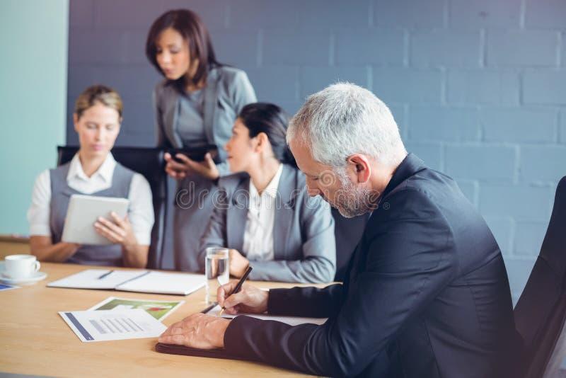 Informe de la escritura del hombre de negocios en la sala de conferencias imagen de archivo