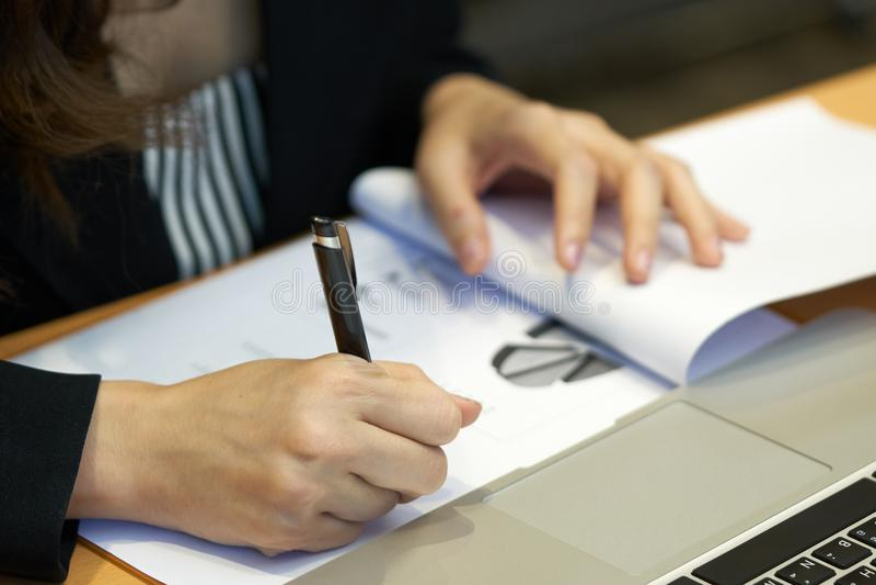 Informe de ventas asiático de la escritura de la empresaria con la pluma negra en el escritorio con un ordenador portátil Y papel imagen de archivo libre de regalías