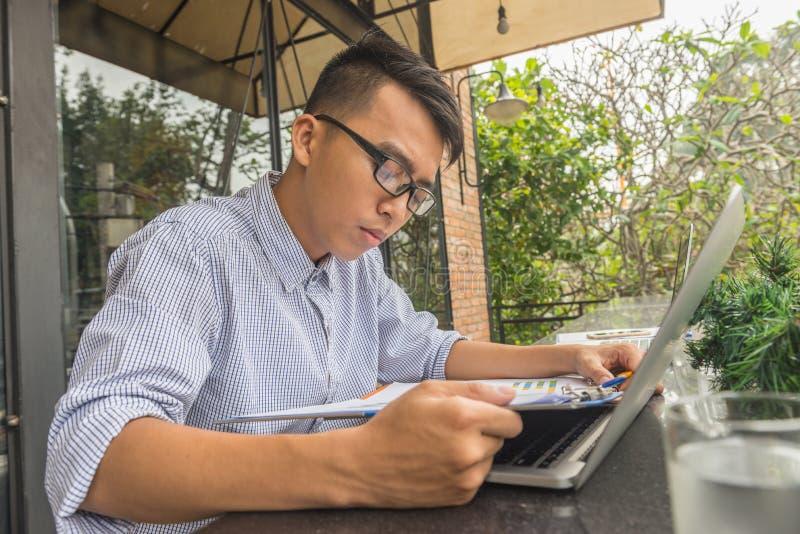 Informe financiero de lectura del hombre de negocios joven foto de archivo
